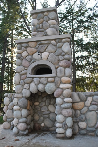 photo of a wood-fired pizza oven, built into a stone chimney on a patio outside